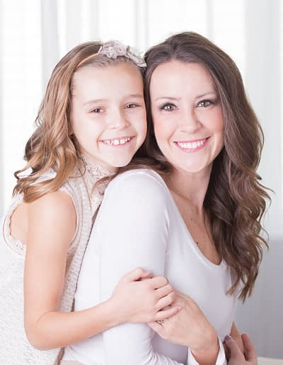 Noblesville Family Photographer captured beautiful daughter embracing her mother in a photo studio that appears to be window lit through white sheers